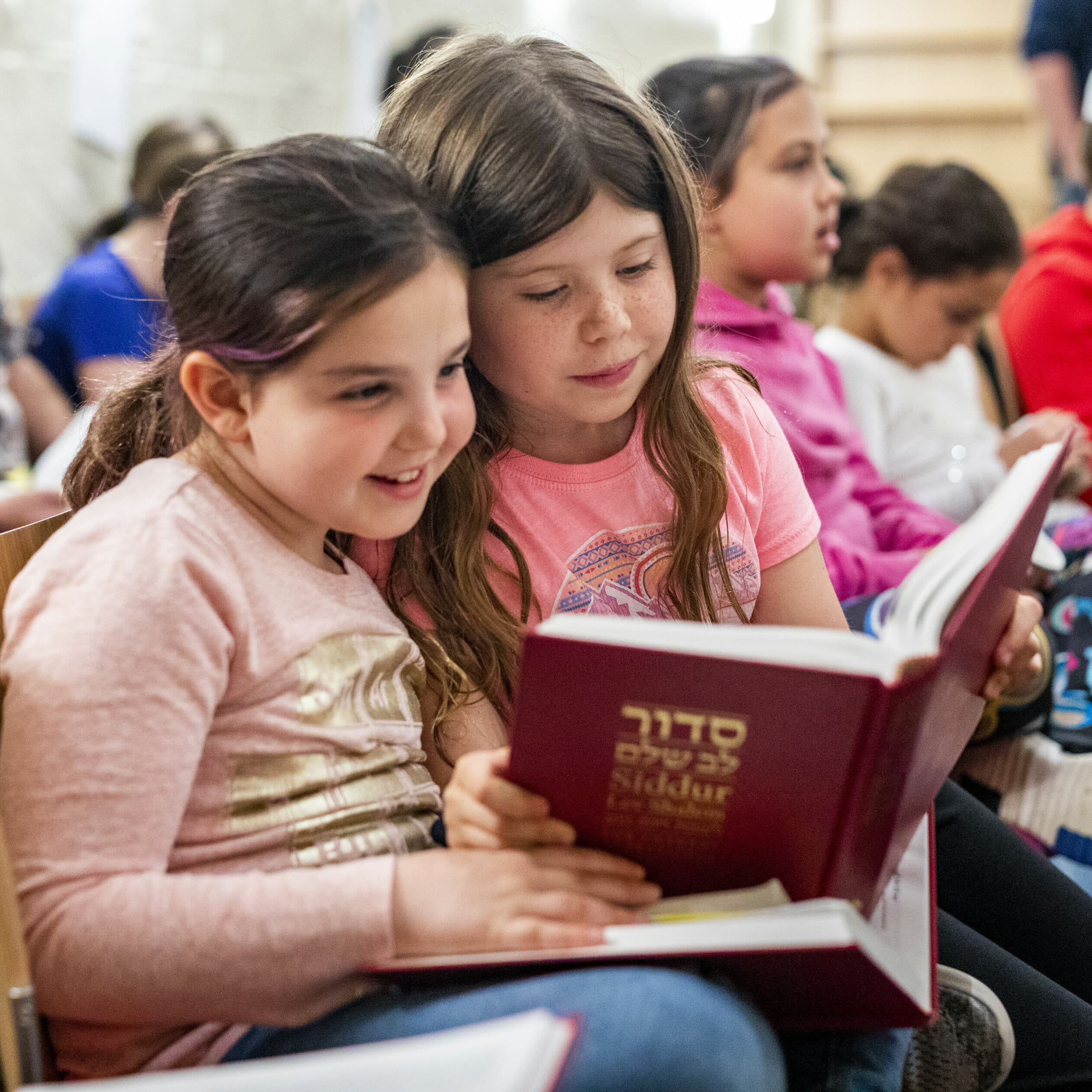 two young girls reading siddur together