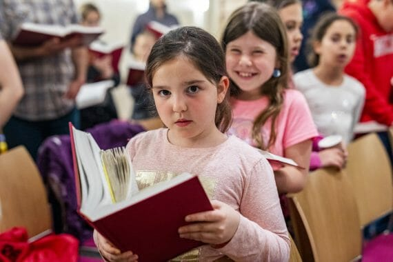 girls smiling while reading siddur