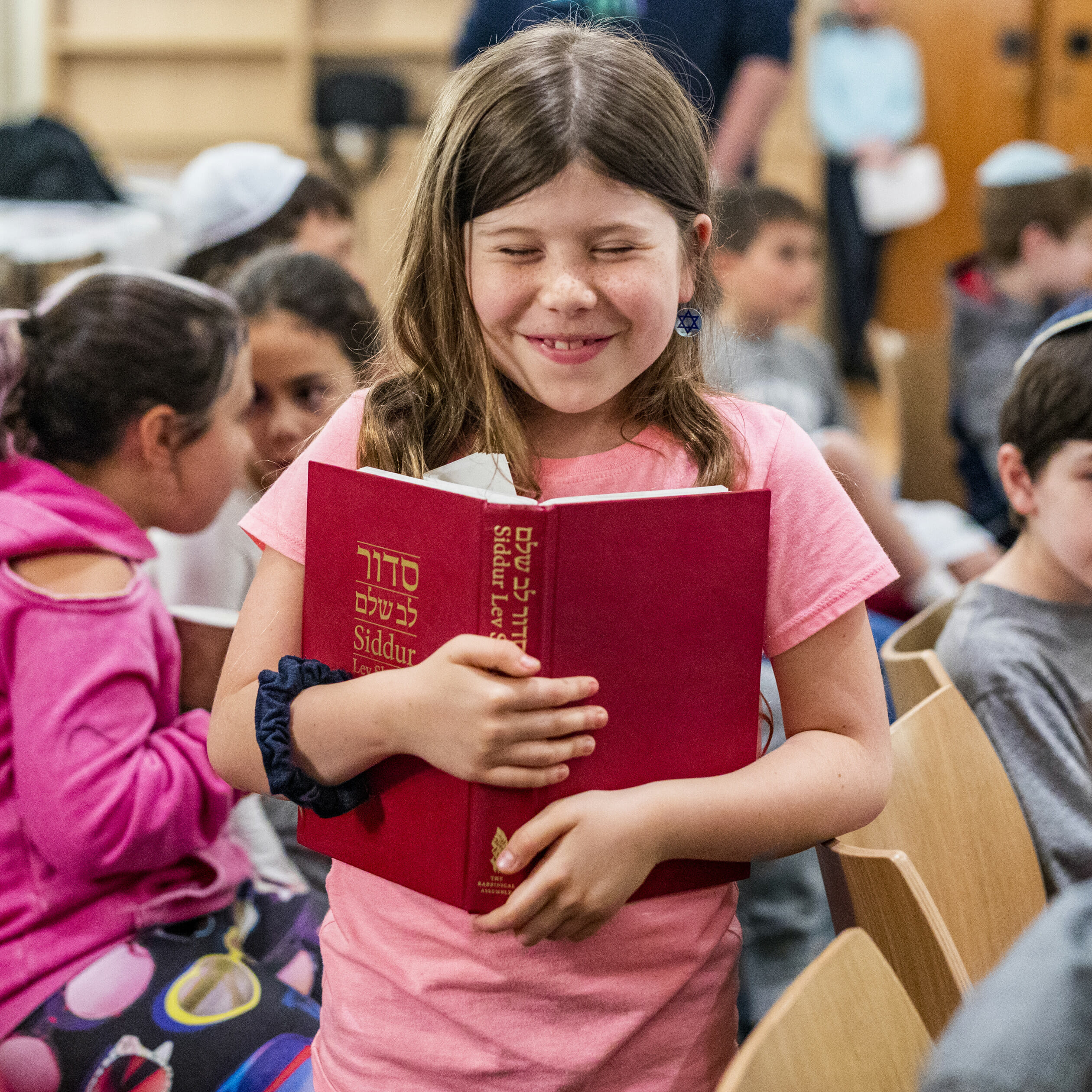 girl closely holding siddur book and smiling
