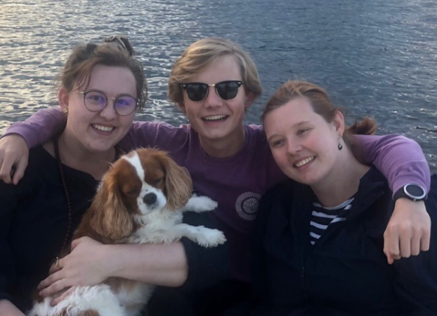 family with a dog on a lake