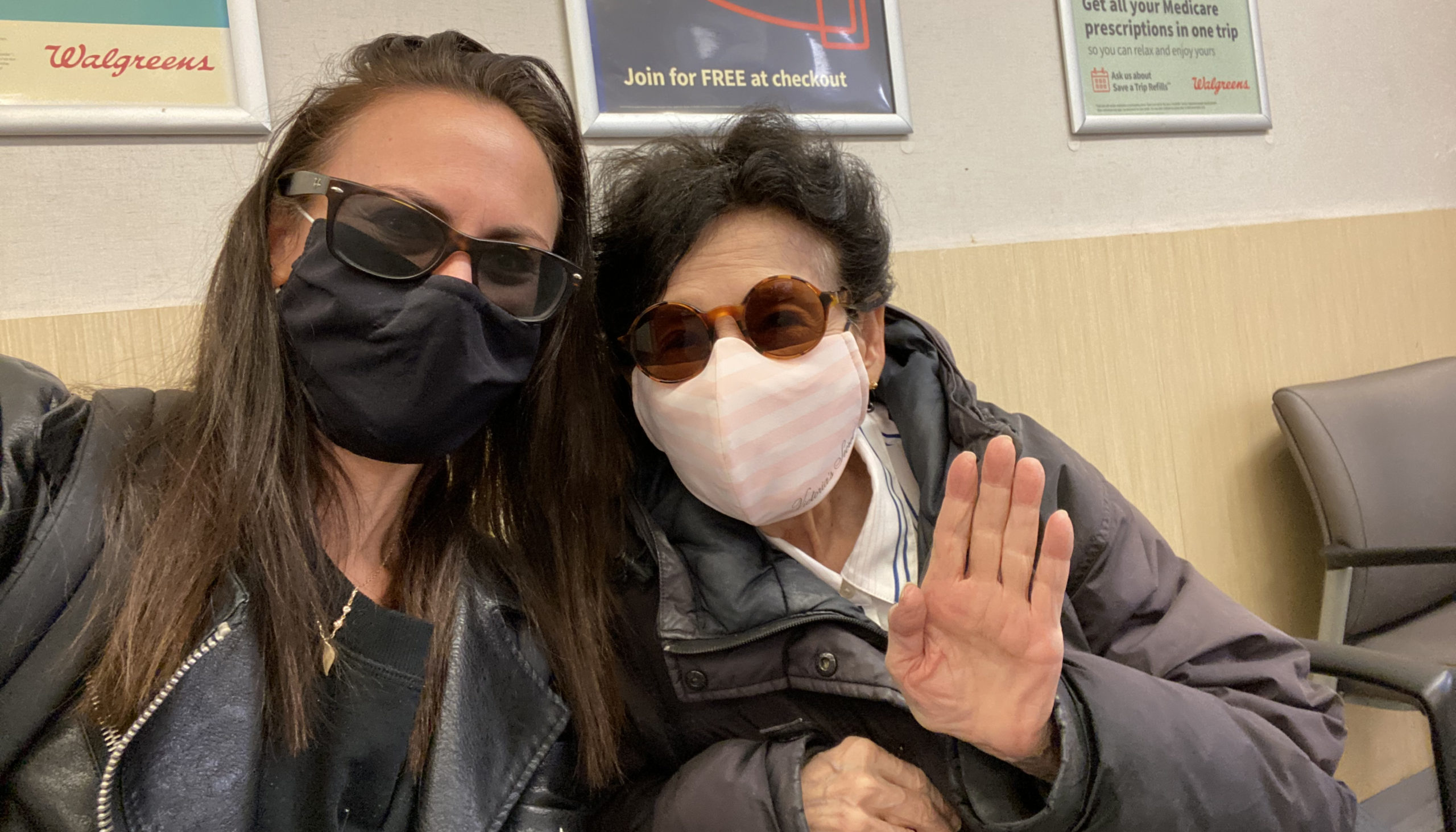 Two women, wearing masks, wait for a vaccine appointment